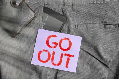 Writing note showing Go Out. Business concept for to spend more time outdoors or in any social event with freedom Smartphone device inside trousers front pocket with wallet