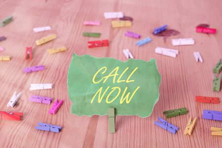 Word writing text Call Now. Business photo showcasing Dialing a contact number immediately to discuss over something Colored clothespin papers empty reminder wooden floor background office