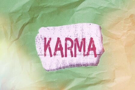 Conceptual hand writing showing Karma. Concept meaning sum of an individual actions in this and previous states of existence Green crumpled colored paper sheet torn colorful background 스톡 콘텐츠