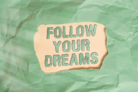 Writing note showing Follow Your Dreams. Business concept for motivational and inspirational expression to pursue your heart desire Green crumpled colored paper sheet torn colorful background