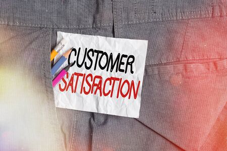 Text sign showing Customer Satisfaction. Business photo showcasing number of users whose experience ratings exceed goals Writing equipment and white note paper inside pocket of man work trousers
