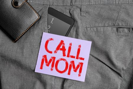 Writing note showing Call Mom. Business concept for Attempting to communicate with the mother using the smartphone Smartphone device inside trousers front pocket with wallet Banque d'images