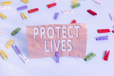 Text sign showing Protect Lives. Business photo text to cover or shield from exposure injury damage or destruction Colored clothespin papers empty reminder blue floor background office pin
