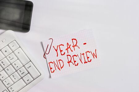 Handwriting text Year end Review. Conceptual photo annual assessment of achievement and goal development White pc keyboard with empty note paper above white background and mobile phone