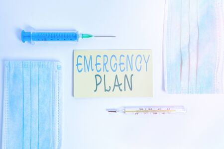 Conceptual hand writing showing Emergency Plan. Concept meaning instructions that outlines what workers should do in danger Set of medical equipment with notepad for health assessment