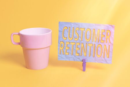 Handwriting text Customer Retention. Conceptual photo activities companies take to reduce user defections Cup empty paper blue clothespin rectangle shaped reminder yellow office