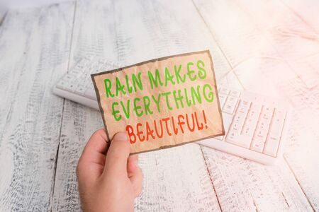 Conceptual hand writing showing Rain Makes Everything Beautiful. Concept meaning raining creates earth a wonderful place Man holding colorful reminder square shaped paper wood floor Banque d'images