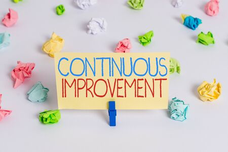 Conceptual hand writing showing Continuous Improvement. Concept meaning making small consistent improvements over time Colored crumpled paper empty reminder white floor clothespin