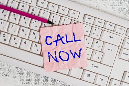 Handwriting text writing Call Now. Conceptual photo Dialing a contact number immediately to discuss over something White keyboard office supplies empty rectangle shaped paper reminder wood