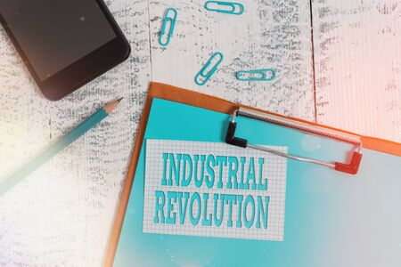 Handwriting text writing Industrial Revolution. Conceptual photo changes in manufacturing and transportation goods Clipboard paper sheet pencil note clips smartphone old wooden background Stockfoto