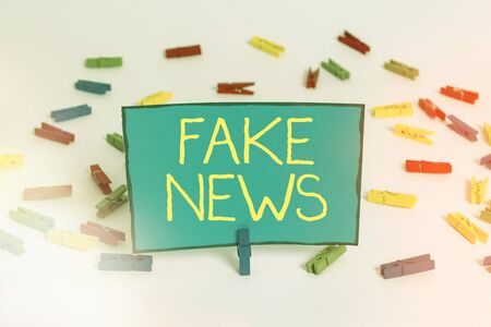 Word writing text Fake News. Business photo showcasing false content published without no credibility to deceive readers Colored clothespin papers empty reminder white floor background office Stock fotó