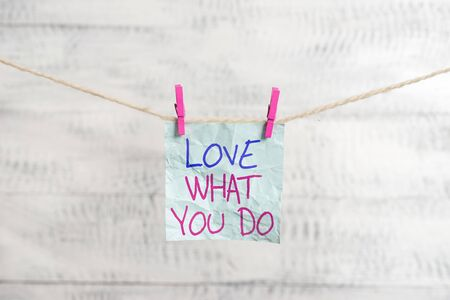 Writing note showing Love What You Do. Business concept for has passion and enthusiasm at work Dedication Devotion Clothesline clothespin rectangle shaped paper reminder white wood desk