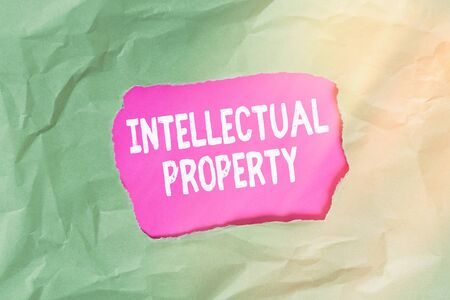 Word writing text Intellectual Property. Business photo showcasing work or invention that is the result of creativity Green crumpled ripped colored paper sheet centre torn colorful background