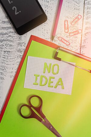 Text sign showing No Idea. Business photo text completely ambivalent with the lack of choices and inspiration Clipboard sheet pencil smartphone scissors note clips wooden background