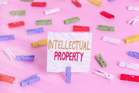 Writing note showing Intellectual Property. Business concept for work or invention that is the result of creativity Colored clothespin papers empty reminder pink floor office pin 版權商用圖片
