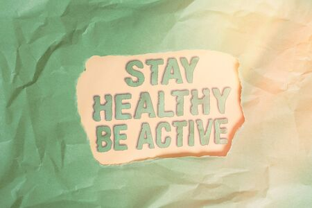 Writing note showing Stay Healthy Be Active. Business concept for physical activity and having energy and strength Green crumpled colored paper sheet torn colorful background