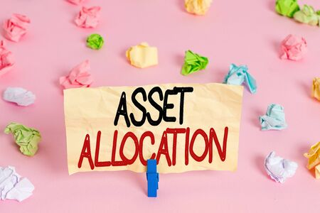 Writing note showing Asset Allocation. Business concept for proportion and implementation strategy to gain advantage Colored crumpled papers empty reminder pink floor background clothespin