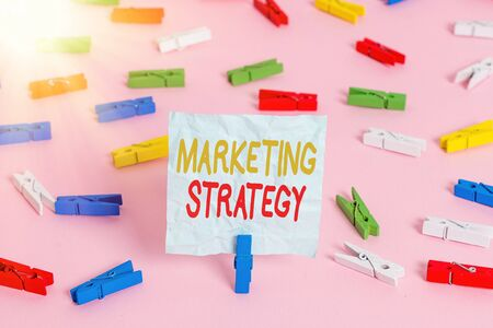 Writing note showing Marketing Strategy. Business concept for plan of action designed to promote and sell product Colored clothespin papers empty reminder pink floor office pin 스톡 콘텐츠