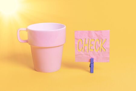 Text sign showing Check. Business photo showcasing examination to test accuracy quality or satisfactory condition Cup empty paper blue clothespin rectangle shaped reminder yellow office