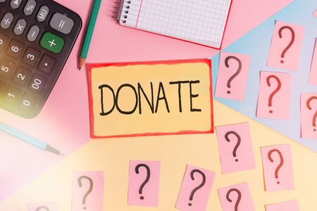 Text sign showing Donate. Business photo text gift for charity to benefit a cause may satisfy medical needs Mathematics stuff and writing equipment above pastel colours background