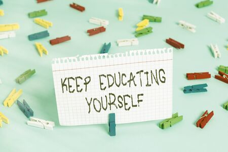 Writing note showing Keep Educating Yourself. Business concept for dont stop studying Improve yourself using Courses Colored clothespin papers empty reminder blue floor officepin Stockfoto