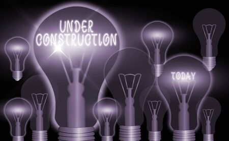 Writing note showing Under Construction. Business concept for building that is unfinished but actively being worked on Realistic colored vintage light bulbs, idea sign solution Фото со стока