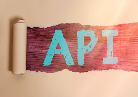 Handwriting text writing Api. Conceptual photo set of routines, protocols, and tools for building software applications Rolled ripped torn cardboard placed above a wooden classic table backdrop