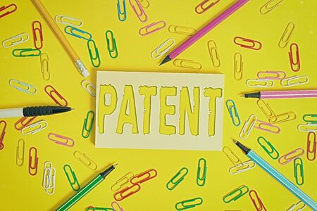 Conceptual hand writing showing Patent. Concept meaning intellectualproperty that gives owner legal right has the sole right Flat lay above empty paper with pencils and paper clips