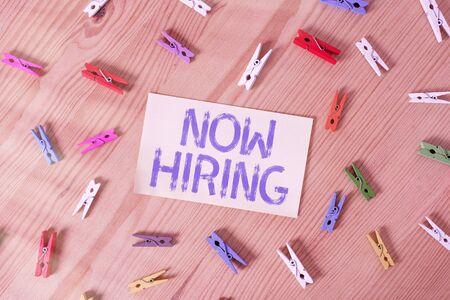 Handwriting text Now Hiring. Conceptual photo an act of starting to employ someone qualified for the position Colored clothespin papers empty reminder wooden floor background office