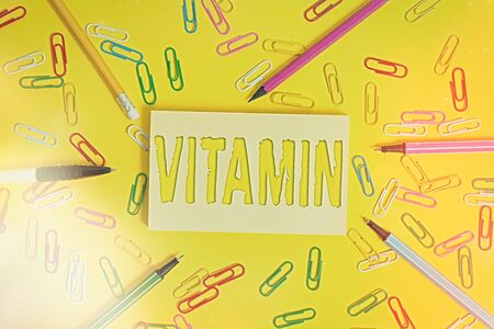 Conceptual hand writing showing Vitamin. Concept meaning organic molecule that is essential micronutrient that organism needs Flat lay above empty paper with pencils and paper clips