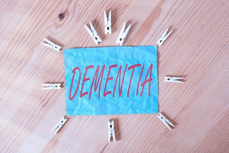 Word writing text Dementia. Business photo showcasing the general word for diseases and disorders with a loss in memory Colored clothespin papers empty reminder wooden floor background office