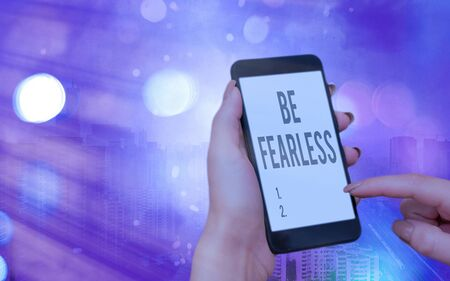 Word writing text Be Fearless. Business photo showcasing act of striving to lead an extraordinary life and make a difference Modern gadgets with white display screen under colorful bokeh background Stock Photo