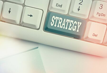 Conceptual hand writing showing Strategy. Concept meaning action plan or strategy designed to achieve an overall goal White pc keyboard with empty note paper above white key copy space Stock Photo