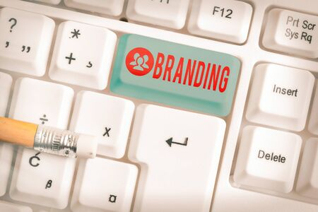 Handwriting text writing Branding. Conceptual photo promotion of product by means of advertising and distinctive design White pc keyboard with empty note paper above white key copy space 版權商用圖片