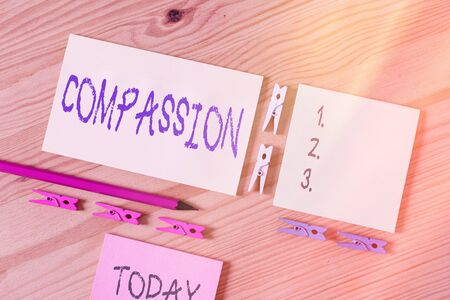 Word writing text Compassion. Business photo showcasing empathy and concern for the pain or misfortune of others Colored clothespin papers empty reminder wooden floor background office