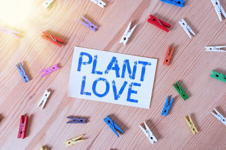 Handwriting text Plant Love. Conceptual photo a symbol of emotional love, care and support showed to others Colored clothespin papers empty reminder wooden floor background office