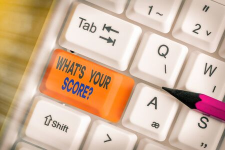 Text sign showing What S Your Score Question. Business photo showcasing Tell Personal Individual Rating Average Results Statistics White pc keyboard with empty note paper above white key copy space