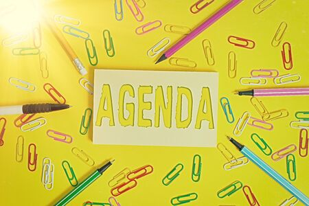 Conceptual hand writing showing Agenda. Concept meaning list of meeting activities in the order which they are to be taken up Flat lay above empty paper with pencils and paper clips