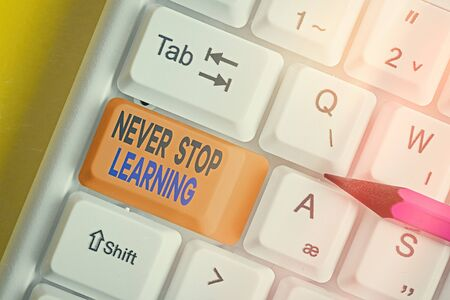 Text sign showing Never Stop Learning. Business photo showcasing continuous education and techniques to be competitive White pc keyboard with empty note paper above white key copy space