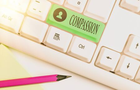 Word writing text Compassion. Business photo showcasing empathy and concern for the pain or misfortune of others White pc keyboard with empty note paper above white key copy space