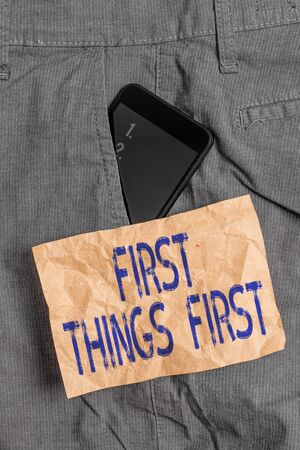 Writing note showing First Things First. Business concept for Business, technology, internet, set your priorities and most important Smartphone device inside trousers front pocket note paper