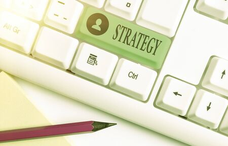 Word writing text Strategy. Business photo showcasing action plan or strategy designed to achieve an overall goal White pc keyboard with empty note paper above white key copy space