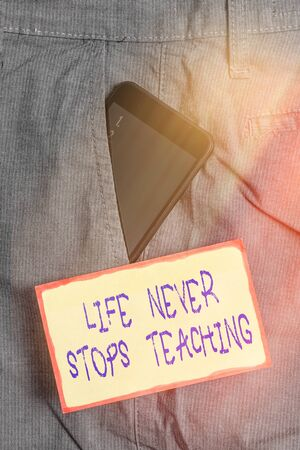 Handwriting text writing Life Never Stops Teaching. Conceptual photo keep learning techniques Look for ways to improve Smartphone device inside formal work trousers front pocket near note paper
