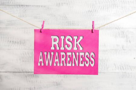 Word writing text Risk Awareness. Business photo showcasing recognizing factors that may cause a lifethreatening effect Clothesline clothespin rectangle shaped paper reminder white wood desk