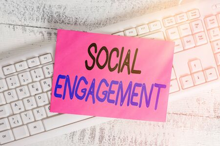 Word writing text Social Engagement. Business photo showcasing refer to degree of participation in a community or society White keyboard office supplies empty rectangle shaped paper reminder wood Foto de archivo