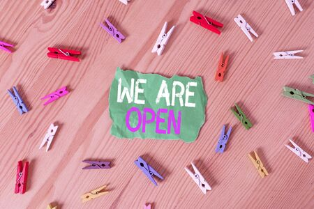 Conceptual hand writing showing We Are Open. Concept meaning no enclosing or confining barrier, accessible on all sides Colored crumpled papers wooden floor background clothespin Stock Photo