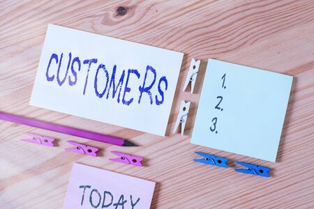 Word writing text Customers. Business photo showcasing individual or organization purchasing products or services Colored clothespin papers empty reminder wooden floor background office Stockfoto
