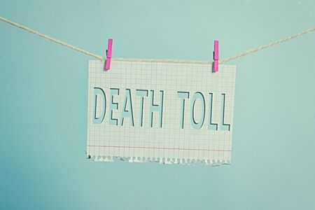 Text sign showing Death Toll. Business photo text the number of deaths resulting from a particular incident Clothesline clothespin rectangle shaped paper reminder white wood desk 스톡 콘텐츠