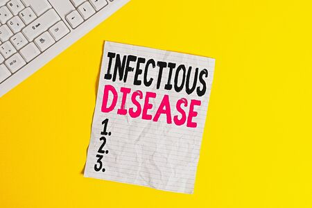 Text sign showing Infectious Disease. Business photo showcasing caused by pathogenic microorganism, such as viruses, etc Copy space on notebook above yellow background with pc keyboard on the table