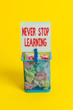 Conceptual hand writing showing Never Stop Learning. Concept meaning continuous education and techniques to be competitive Trash bin crumpled paper clothespin office supplies yellow Standard-Bild